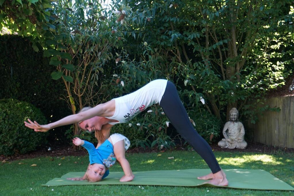 Yoga Personal Trainerin aus Frankfurt übt Postnatal Yoga mit Kind im Garten Teaser